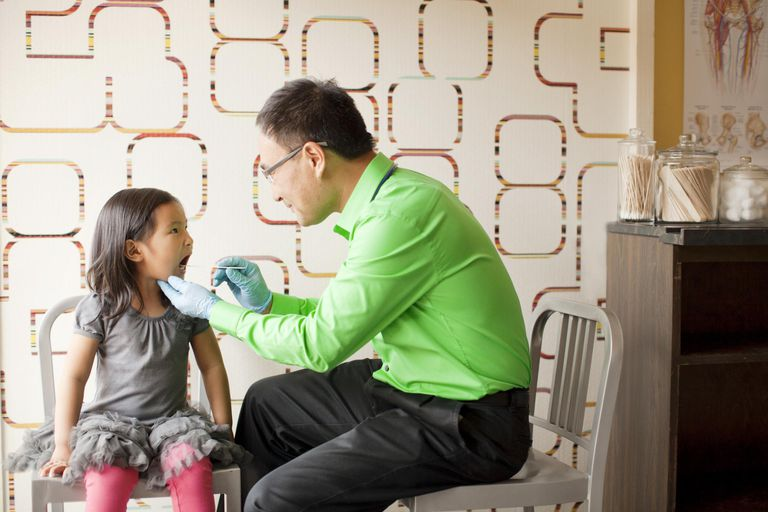 Doctor uses tongue depressor to look in child's mouth