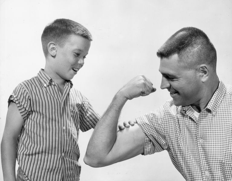 Boy feels his father's muscle and appreciates his manliness.