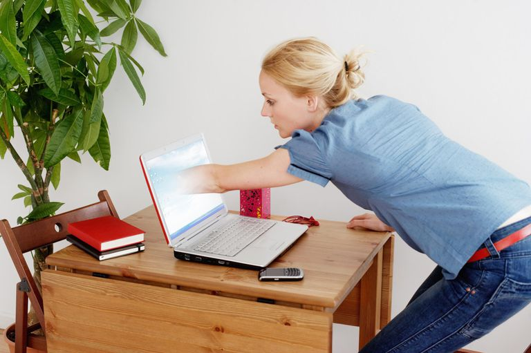 Young woman reaching arm into laptop screen