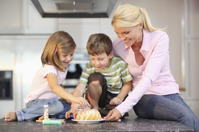 Mother and her two children decorating a cake together