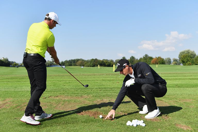 Pro golfer Nicolas Colsaerts (right) gives a golf lesson to racing driver Patrick Pilet