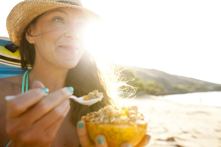 woman eating cereal at the beach