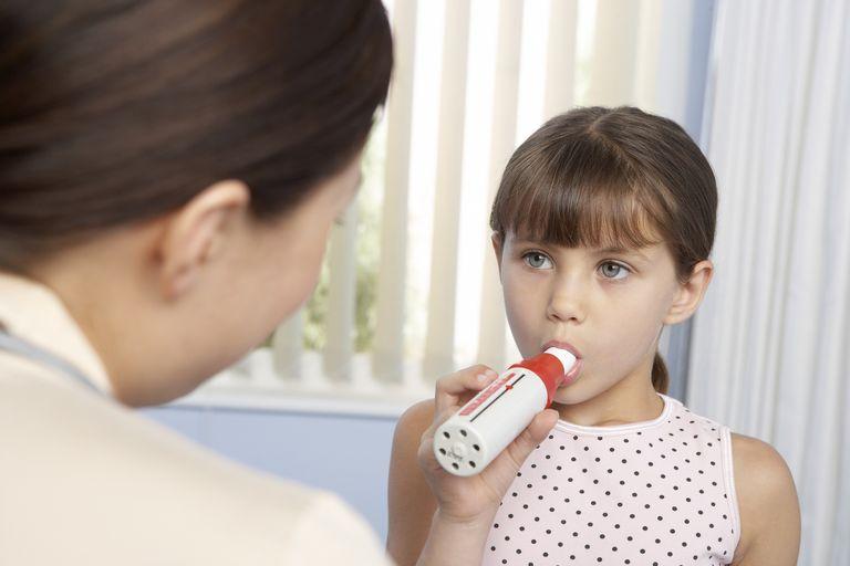 girl breathing into peak flow meter (spirometer)