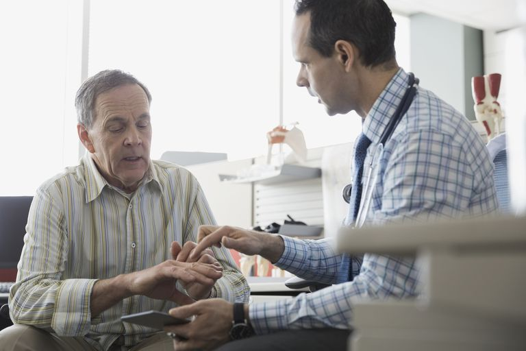A senior working with a doctor in an office.