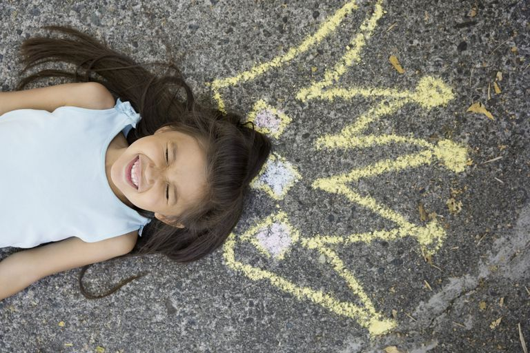 Enthusiastic girl with sidewalk chalk crown overhead