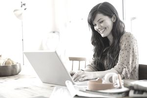 Smiling woman using laptop at table