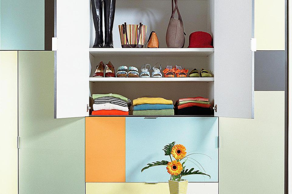 Open cupboard containing neatly stacked clothing in untidy room