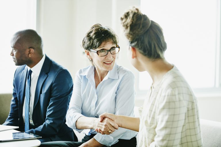 Smiling mature businesswoman shaking hands with colleague after meeting in office