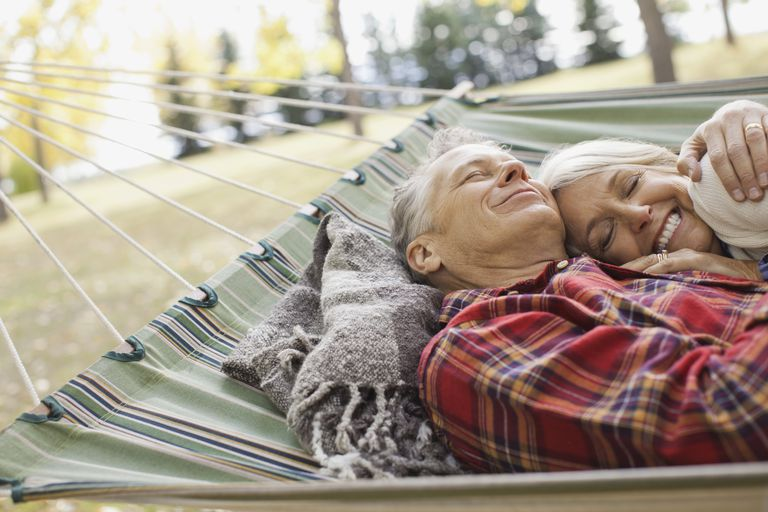 Loving mature couple lying in hammock at park
