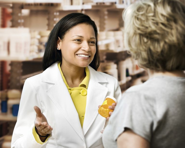 pharmacist handing medication to a customer