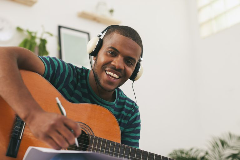 Portrait of smiling man with guitar hearing music with headphones