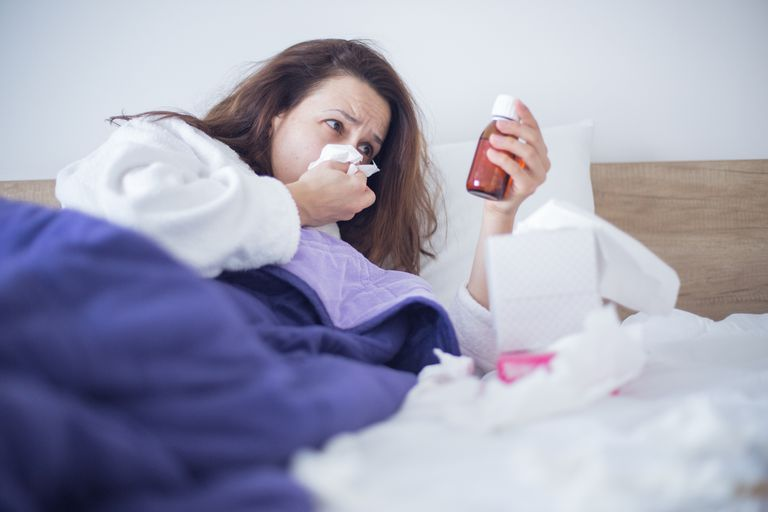 Woman holding bottle of cold meds