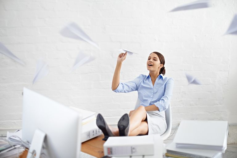 Shot of a young businesswoman throwing paper planes while sitting at her desk