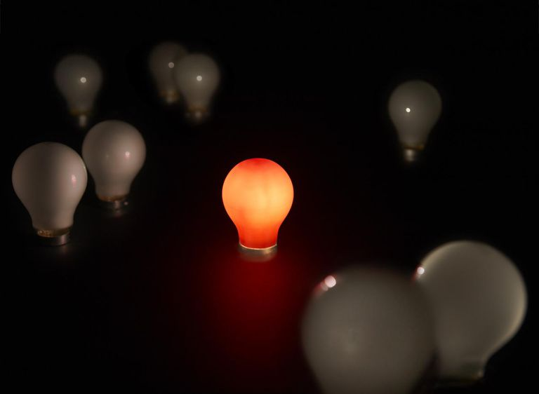 A red lightbulb lit amongst unlit white bulbs