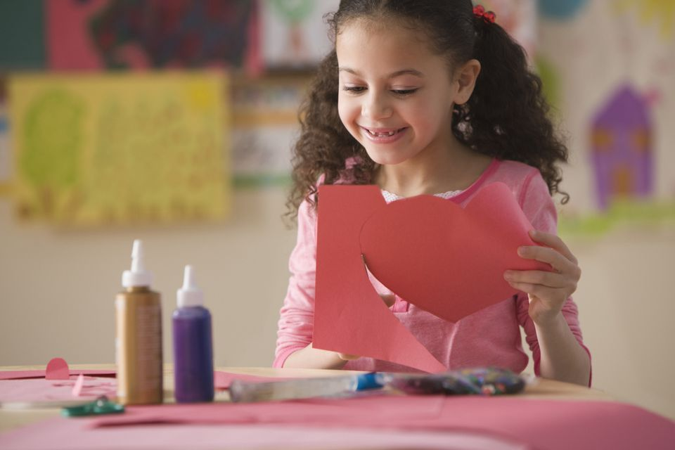 Hispanic girl cutting out Valentine's heart in classroom