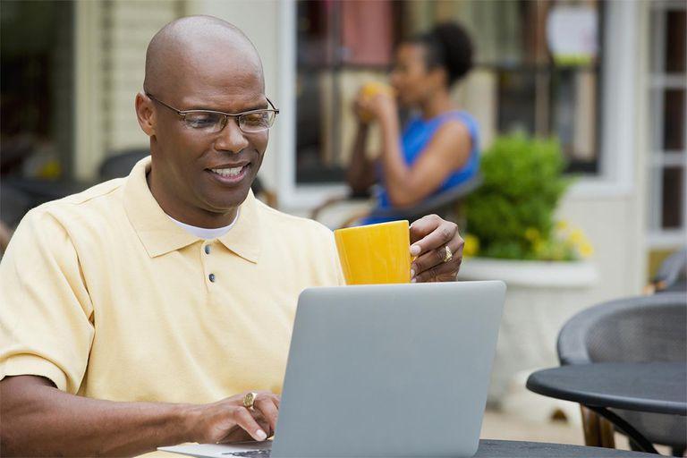Black man using laptop at sidewalk cafe