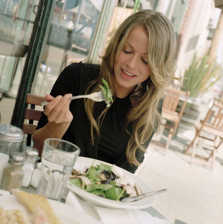 Young woman eating salad at cafe