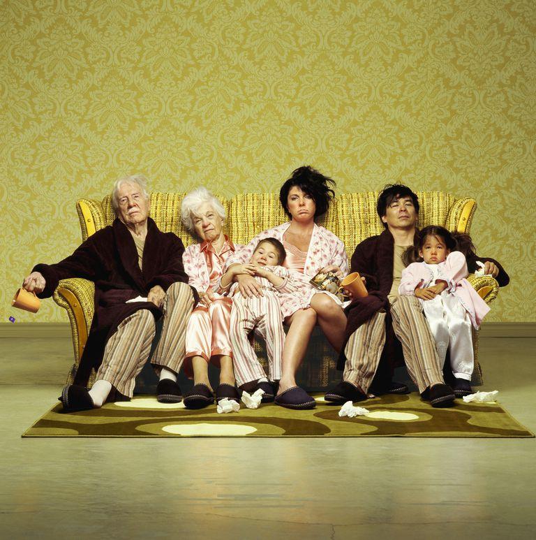 Three generation family sitting sick in sofa