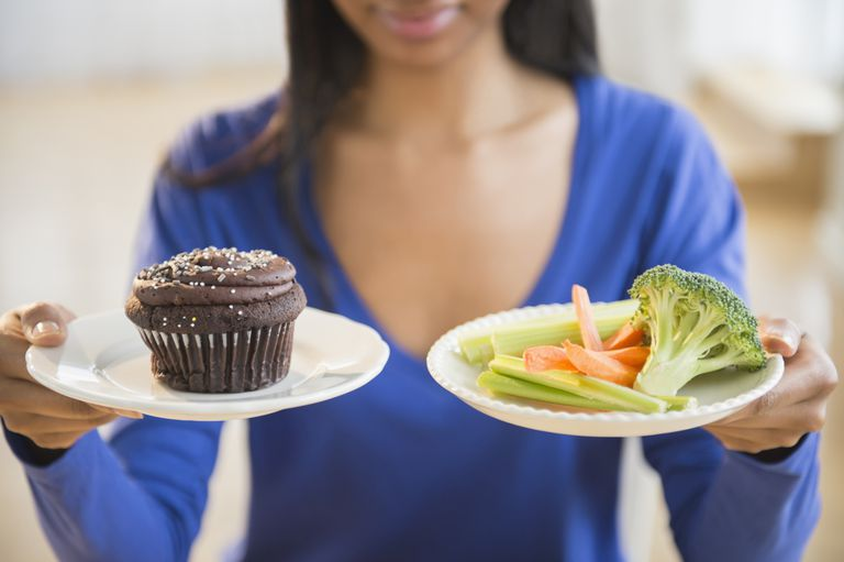 Woman holding cupcakes and vegetables