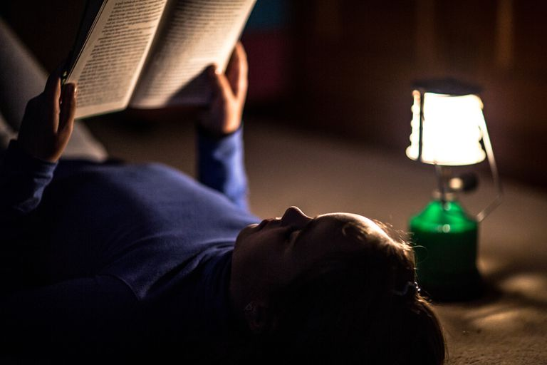 Girl reading book by lamp light