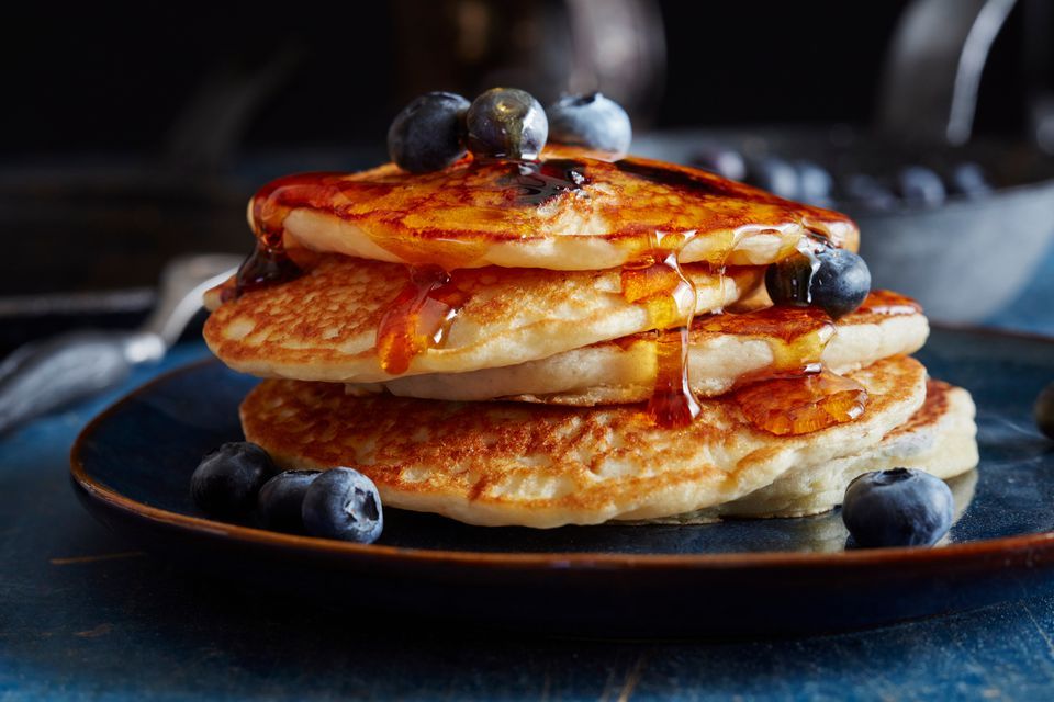 Homemade pancakes topped with maple syrup and fresh blueberries