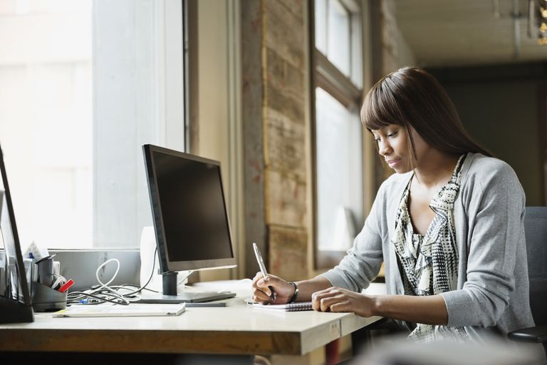 Female entrepreneur working at desk in creative office space
