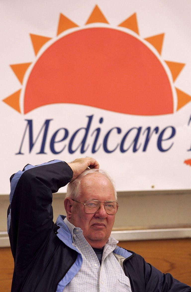 Older man sitting under a Medicare banner scratching his head