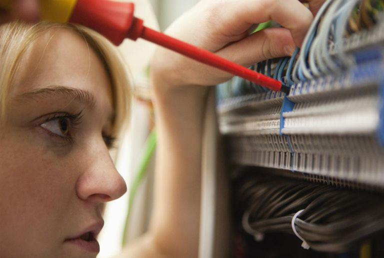 Close-up of young female electrician working