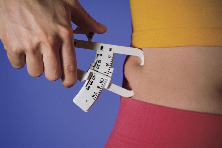 Woman measuring percentage of body fat on waist