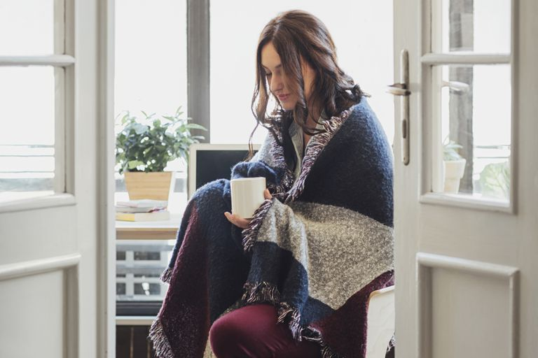 Woman wrapped in blanket holding mug