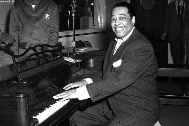 Duke Ellington, a famous jazz musician, poses with his piano at the KFG Radio Studio. 3 November 1954