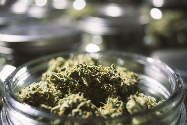 Close Up Marijuana Buds in Glass Jar with Blurry Background