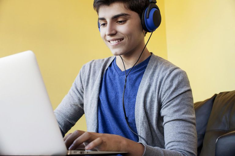 Teenage boy using laptop and listening to headphones