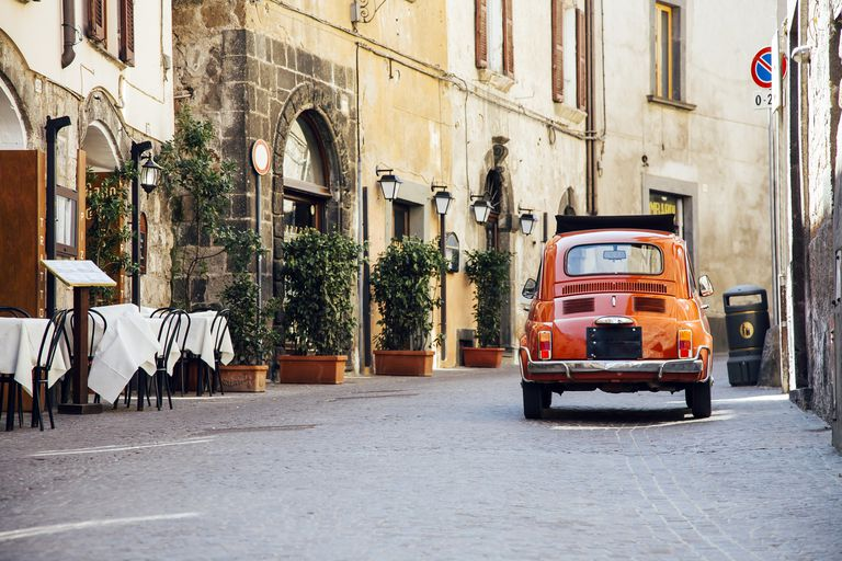 Old red vintage car on the narrow street in Italy