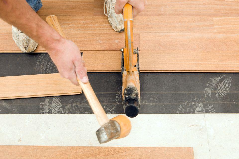 Worker Installing New Cumuru Hardwood Floor