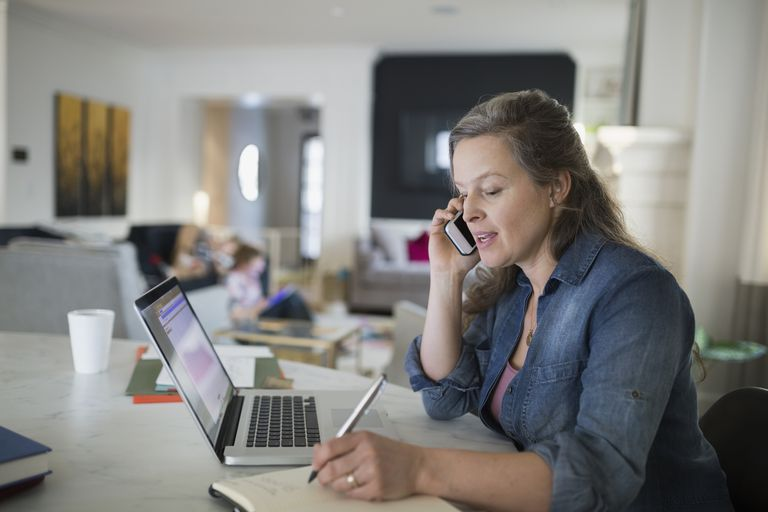 woman talking on cell phone writing next to laptop