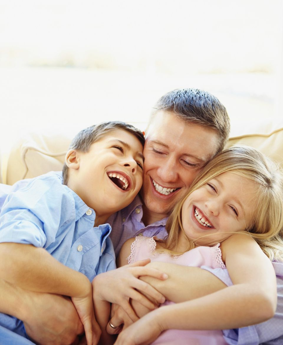 Happy father playing with two children on couch