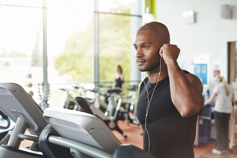 Man in gym on treadmill putting head phone in