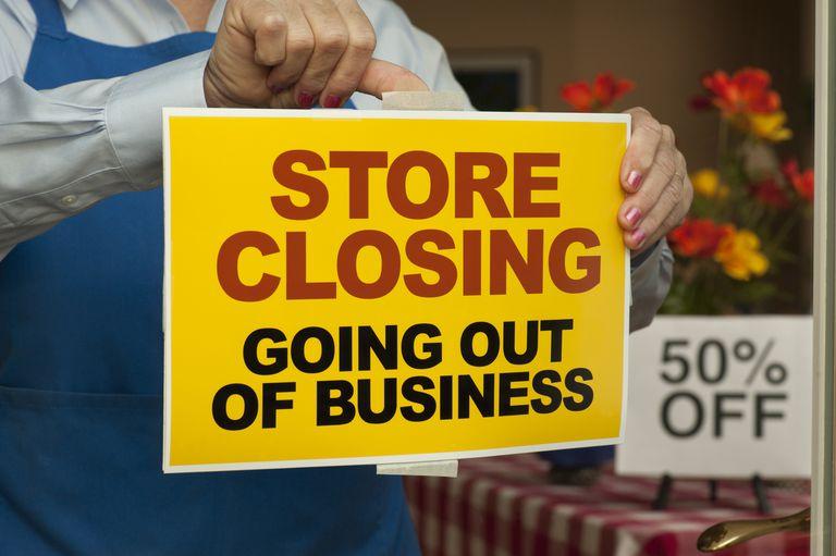 Store Closing sign being placed on a shop window.