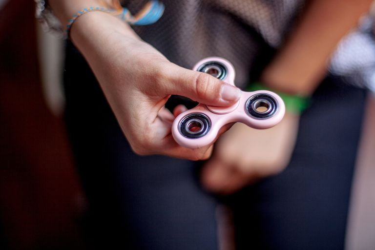 spinner.Teen girl playing with toy