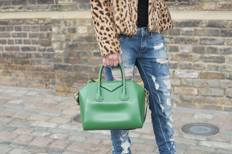 Street style photo of woman in distressed jeans and leopard coat