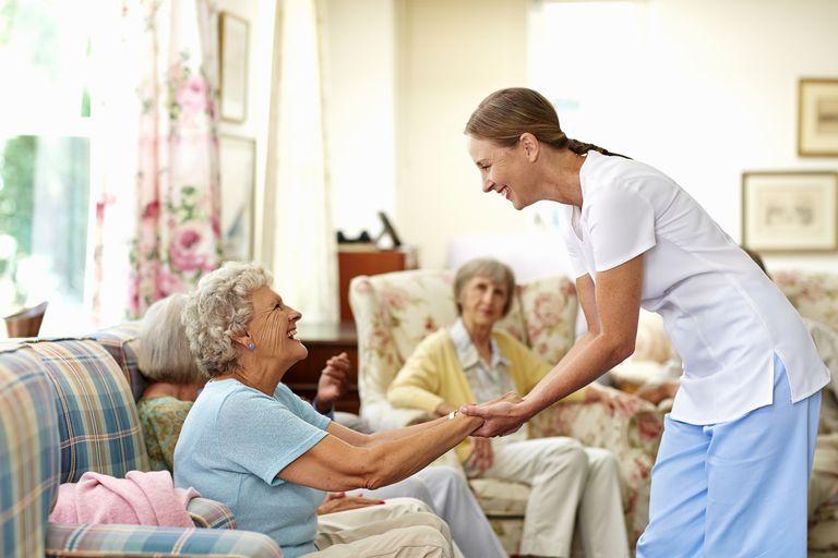 Happy caretaker assisting senior woman