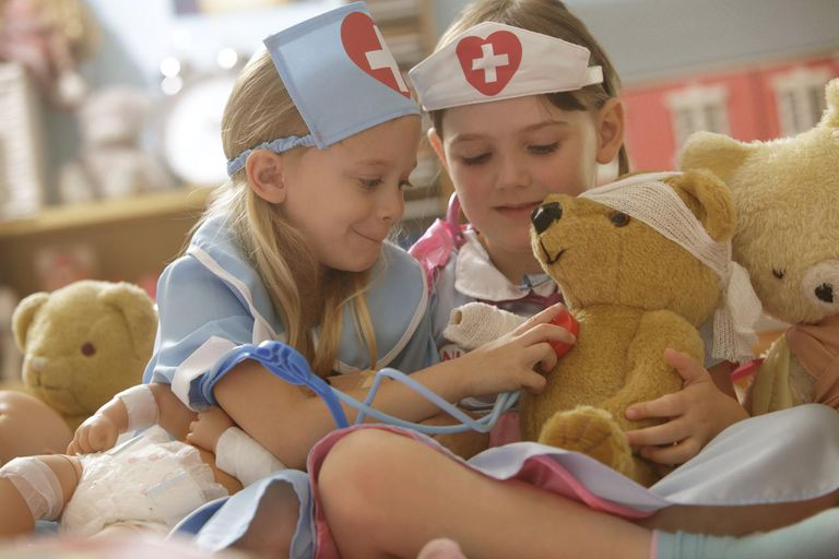 Two girls playing nurse with toys