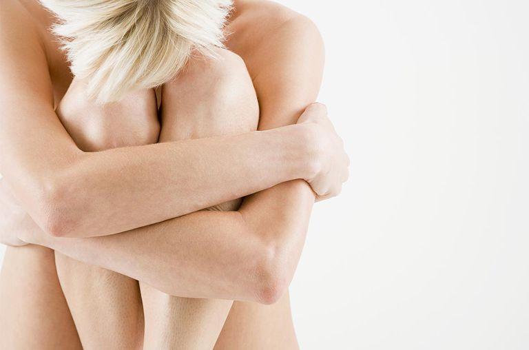 Nude woman hugging her legs