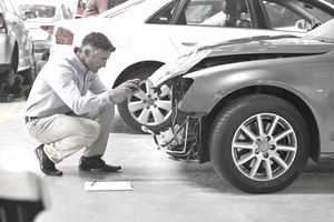 Insurance employee inspecting damage on a car