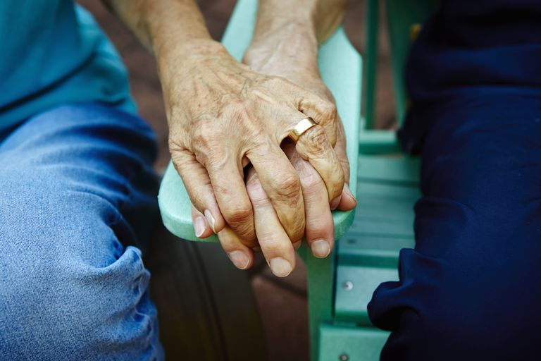 Cropped close up of senior couple hands holding on park bench