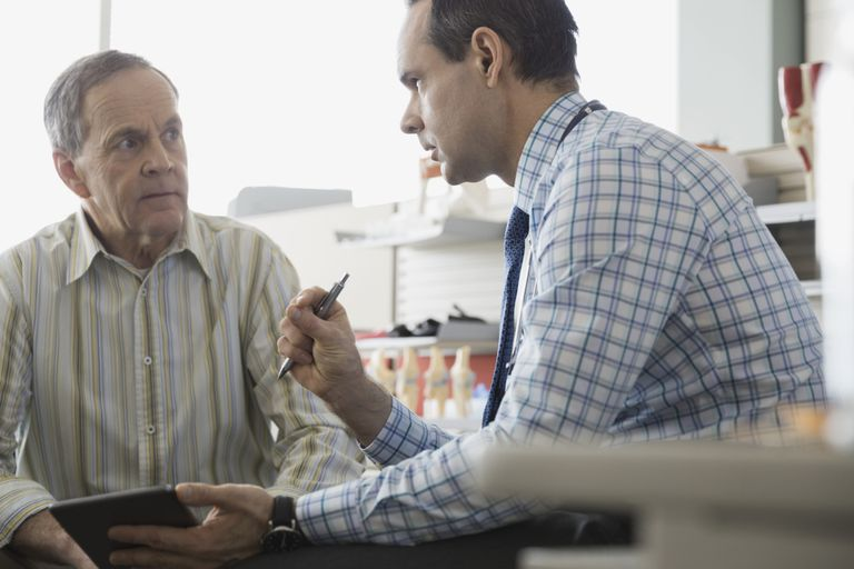 Doctor talking with senior patient in office