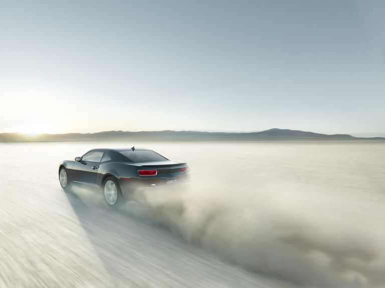 Black sports car driving on dry lake bed