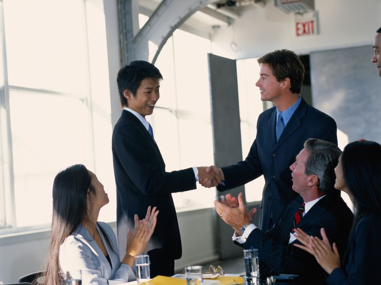Business colleagues in board room, men greeting