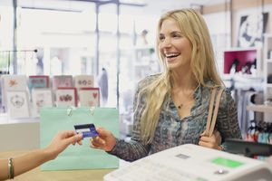 Woman paying with credit card in clothing store